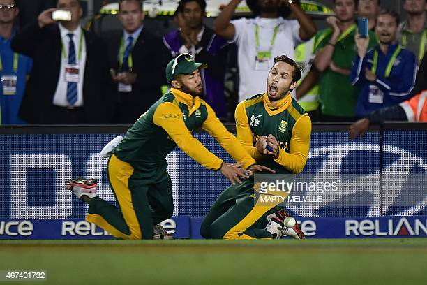 South Africa's Farhaan Behardien trys to take a catch but is hit by teammate JeanPaul Duminy during the Cricket World Cup semifinal match between New...