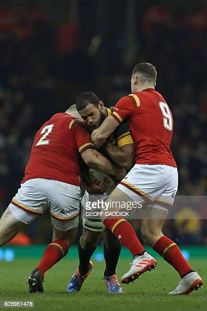 South Africa's flanker Nizaam Carr is tackled by Wales' hooker Ken Owens and Wales' scrumhalf Gareth Davies during the rugby union test match between...