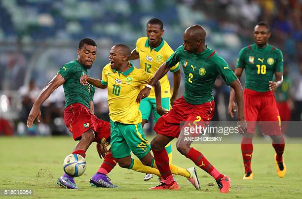 South Africa's forward Thulani Serero is tackled by Cameroon's defender Allan Nyom and defender JeanPatrick Abouna during the African Cup of Nations...