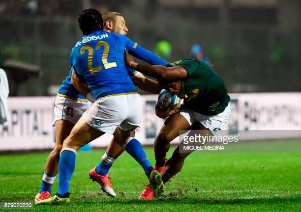 South Africa's fullback Warrick Gelant runs to evade Italy's flyhalf Ian McKinley and Italy's fullback Matteo Minozzi during a rugby union test match...