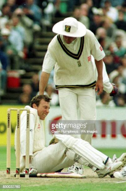 South Africa's Hanse Cronje offers a helping hand to England's opener Mike Atherton after a bounce from Lance Klusener left him grounded during play...