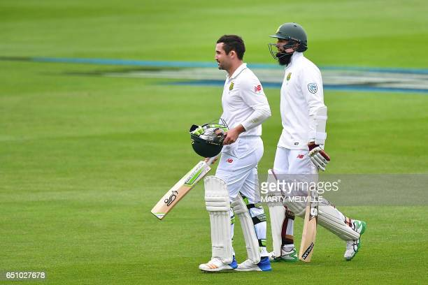 South Africa's Hashim Amla and Dean Elgar walk from the field after bad light ends play for day three of the first international cricket test match...
