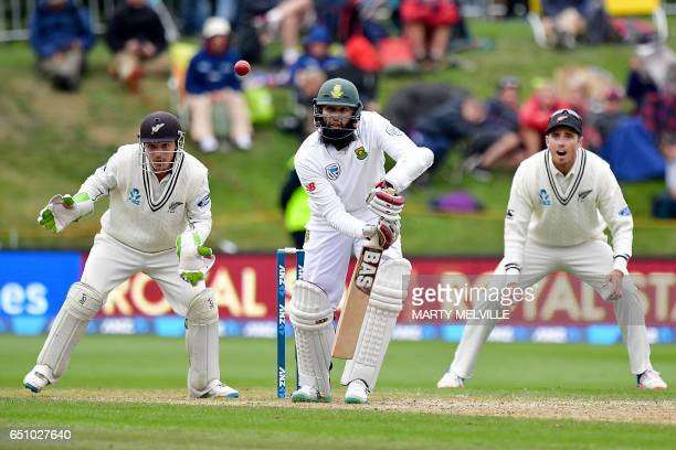 South Africa's Hashim Amla bats watched by New Zealand's Tim Southee and keeper BJ Watling during day three of the first international cricket test...