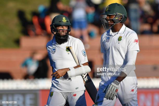 South Africa's Hashim Amla walks from the field with teammate Kagiso Rabada at the end of the day's play during the second Test cricket match between...