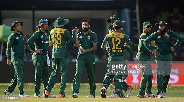 South Africa's Imran Tahir celebrates with teammates after his dismissal of unseen India's Suresh Raina during the first one day international...