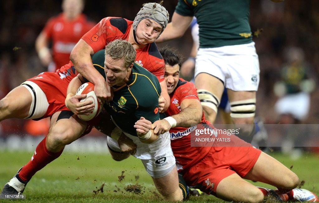 South Africa's Jean de Villiers (C) goes over for a try despite the efforts of Wales' Jonathan Davies (L) and Wales' Mike Phillips (R) during the International rugby union test match between Wales and South Africa at the Millennium Stadium in Cardiff, south Wales, on November 9, 2013.