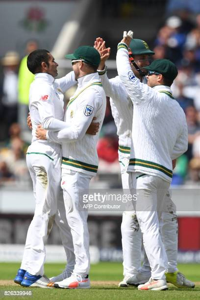 South Africa's Keshav Maharaj celebrates with teammates after taking the wicket of England's Alastair Cook during play on the day 1 of the fourth...