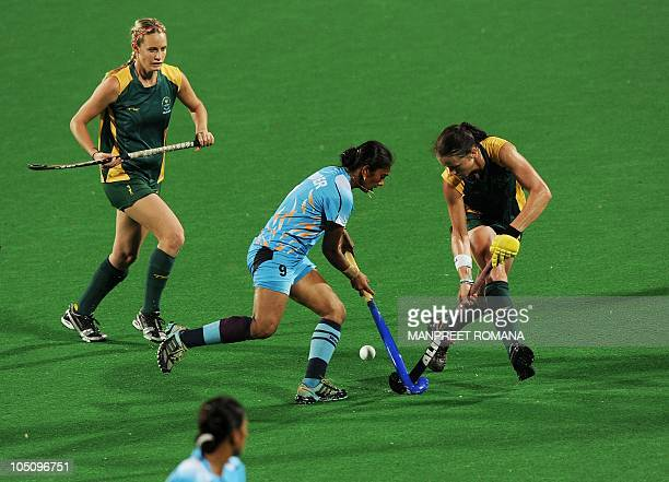 South Africa's Kim Hubach fights for the ball with India's Surinder Kaur during their field hockey match at the Major Dhyan Chand National Stadium...
