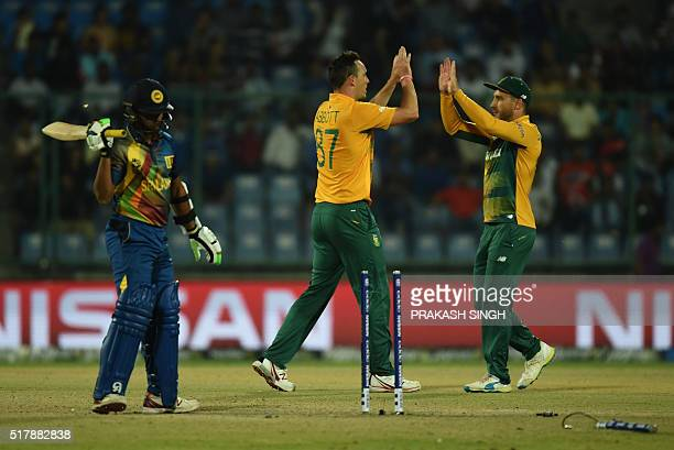 South Africa's Kyle Abbottcelebrates the wicket of Sri Lanka's batsman Jeffrey Vandersay with captain Faf du Plessis during the World T20 cricket...