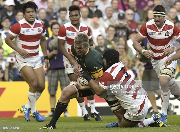South Africa's lock PieterSteph du Toit is tackled by Japan's prop Kensuke Hatakeyama during a Pool B match of the 2015 Rugby World Cup between South...