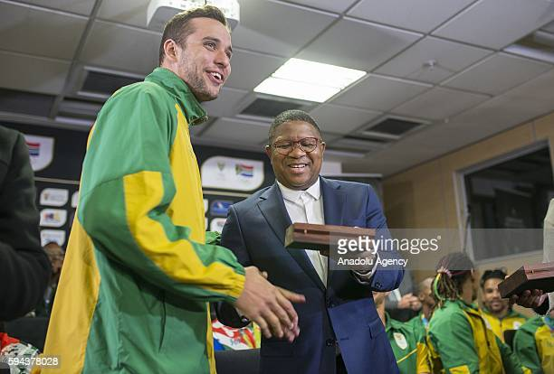 South Africa's Minister of Sport and Recreation Fikile Mbalula congratulates Chad le Clos who won two silver medals in Men's 100m butterfly stroke...