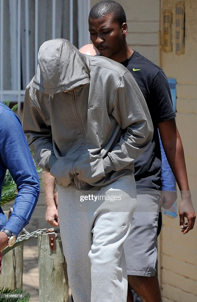 South Africa's Olympic sprinter Oscar Pistorius (L) leaves the Boshkop police station on February 14, 2013 in Pretoria East, to be taken into police custody after allegedly shooting dead his model girlfriend having mistaken her for an intruder at his upscale home.
