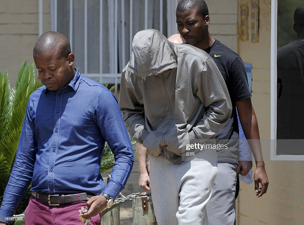 South Africa's Olympic sprinter Oscar Pistorius (C) leaves the Boshkop police station on February 14, 2013 in Pretoria East, to be taken into police custody after allegedly shooting dead his model girlfriend having mistaken her for an intruder at his upscale home.
