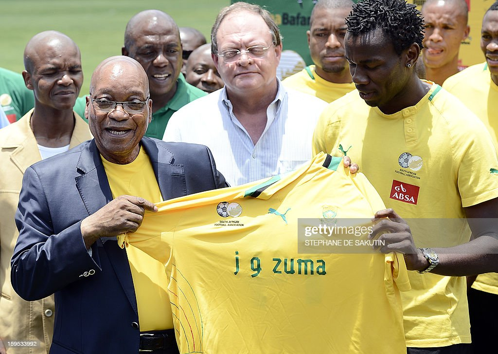 South Africa's President Jacob Zuma (L) receives a team jersey from the South African football team captain Bongani Khumalo (R) on January 15, 2013 at Orlando Stadium in Soweto. Zuma visited today the National Football Team, dubbed the Bafana Bafana at their training camp in Soweto to assure them of the nation's support ahead of the 2013 African Cup of Nations that will take place in South Africa from January 19 to February 10. AFP PHOTO / STEPHANE DE SAKUTIN