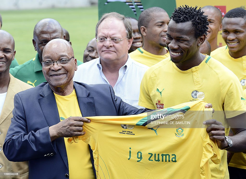 South Africa's President Jacob Zuma (L) receives a team jersey from the South African football team captain Bongani Khumalo (R) on January 15, 2013 at Orlando Stadium in Soweto. Zuma has visited today the National Football Team, dubbed the Bafana Bafana at their training camp in Soweto to assure them of the nation's support ahead of the 2013 African Cup of Nations that will take place in South Africa from January 19 to February 10.