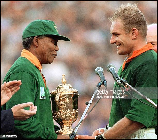 South Africa's president Nelson Mandela congratulates South Africa's rugby team captain François Pienaar before handing him the Webb Ellis Cup after...