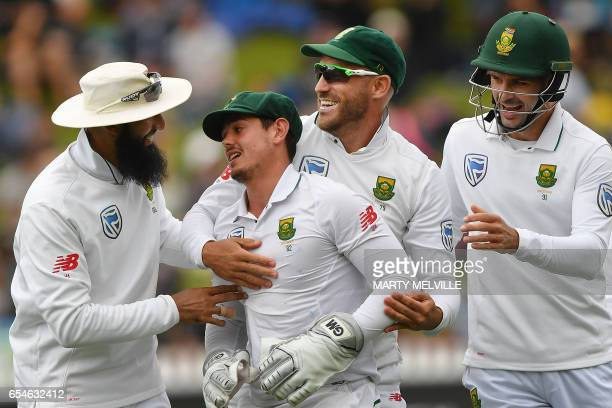 South Africa's Quinton de Kock celebrates catching New Zealand's Neil Broom with teammates Hashim Amla captain Faf du Plessis and Stephen Cook during...