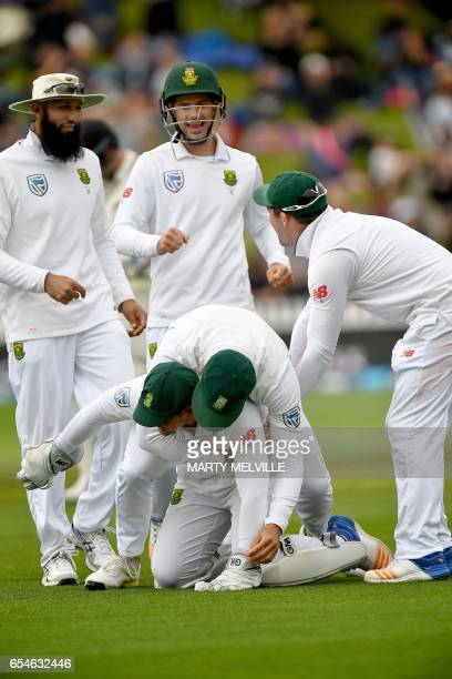 South Africa's Quinton de Kock celebrates catching New Zealand's Neil Broom with teammates captain Faf du Plessis Hashim Amla Stephen Cook and Dean...