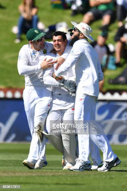 South Africa's Quinton de Kock celebrates taking the catch of New Zealand's Neil Broom with team mates Dean Elgar and Hashim Amla during the 2nd...