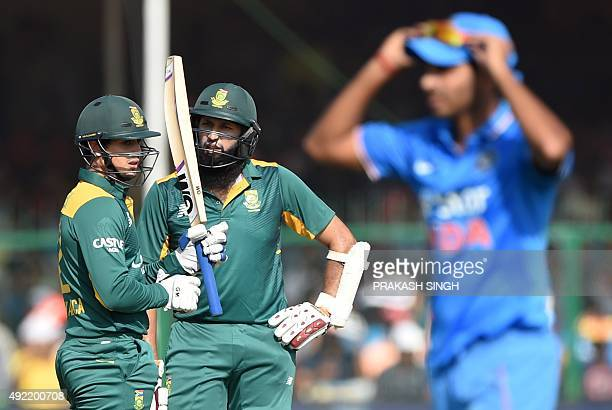South Africa's Quinton de Kock speaks with teammate Hashim Amla as India's Bhuvneshwar Kumar walks past during the first one day international...