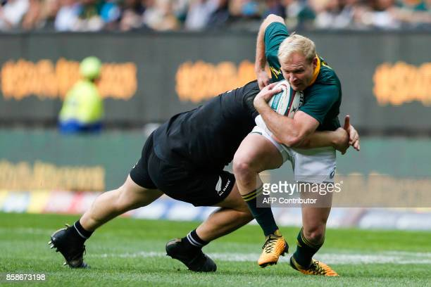 South Africa's scrumhalf Ross Cronje is tackled by New Zealand's flyhalf Damian McKenzie during the Rugby test match between South Africa and New...
