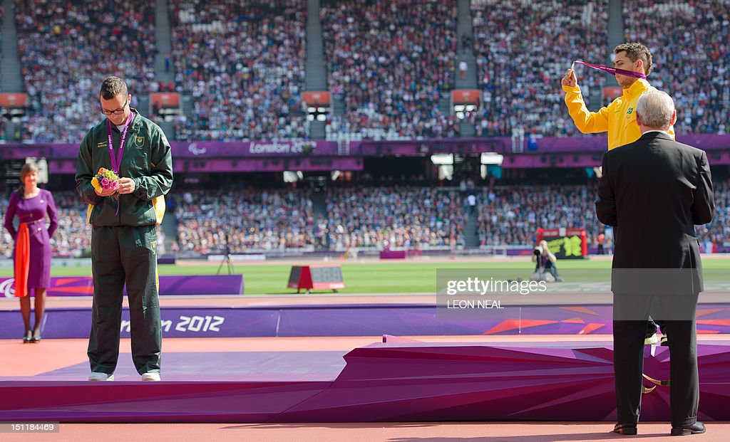 South Africa's silver medallist Oscar Pistorius (L) looks down as Brazil's Alan Fonteles Oliveira (R) holds up his gold medal on the podium during the medal ceremony of the men's 200m T44 athletics event at the London 2012 Paralympic Games at the Olympic Stadium in east London on September 3, 2012. Pistorius apologised on September 3 for the timing of his outburst after losing his T44 200m title, but insisted there was an issue with large prosthetics lengthening an amputee's stride. Pistorius, the star of the London 2012 Paralympics, was sensationally beaten into the silver medal position by Brazil's Alan Oliveira on September 2, in a result that stunned the Olympic Stadium. The 25-year-old then hit out at the International Paralympic Committee (IPC), claiming it was not a fair race and he was at a disadvantage caused by artificial leg length, as the regulations allowed athletes to make themselves 'unbelievably high'.