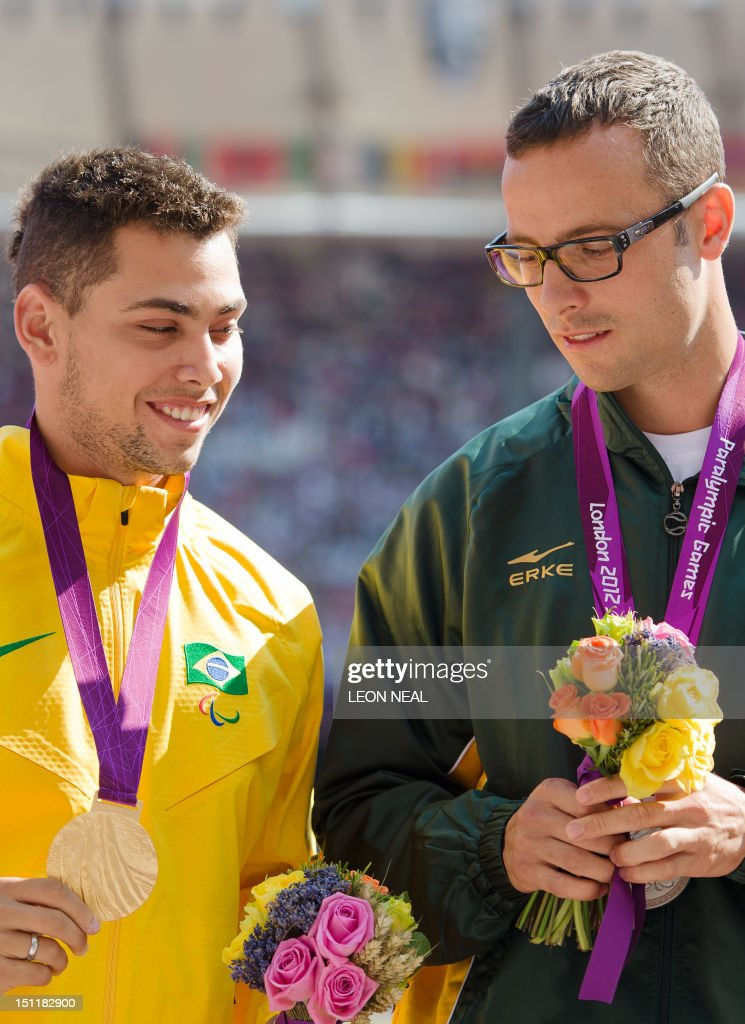 South Africa's silver medallist Oscar Pistorius (R) looks down toward the gold medal of Brazil's Alan Fonteles Oliveira (L) on the podium during the medal ceremony of the men's 200m T44 athletics event at the London 2012 Paralympic Games at the Olympic Stadium in east London on September 3, 2012. Pistorius apologised on September 3 for the timing of his outburst after losing his T44 200m title, but insisted there was an issue with large prosthetics lengthening an amputee's stride. Pistorius, the star of the London 2012 Paralympics, was sensationally beaten into the silver medal position by Brazil's Alan Oliveira on September 2, in a result that stunned the Olympic Stadium. The 25-year-old then hit out at the International Paralympic Committee (IPC), claiming it was not a fair race and he was at a disadvantage caused by artificial leg length, as the regulations allowed athletes to make themselves 'unbelievably high'.