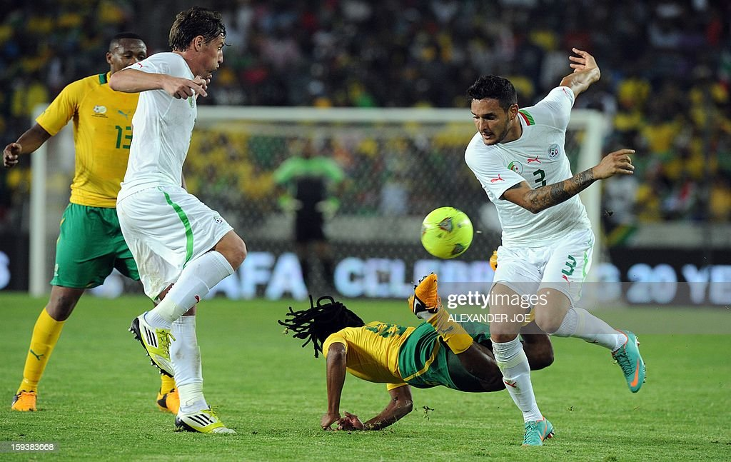 South Africa's Siphiwe Tshabalala (C) falls next to Algeria's Liassine Cadamuro (R) during a friendly football match between South Africa's Bafana Bafana and Algeria in Soweto on January 12 , 2013, ahead of the 2013 African Cup of Nations that will take place in South Africa from January 19 to February 10.