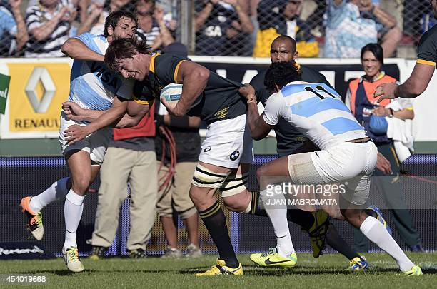 South Africa's Springboks' lock Eben Etzebeth is tackled by Argentina's Los Pumas' wing Manuel Montero and fly half Nicolas Sanchez during their...