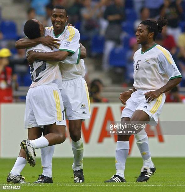 South Africa's Teboho Mokoena is congratulated by captain Lucas Radebe as McBeth Sibaya joins in 02 June 2002 in their Group B match in Busan...