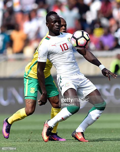 South Africa's Tiyani Mabunda vies with Senegal Sadio Mane during the 2018 World Cup qualifying football match between South Africa and Senegal on...