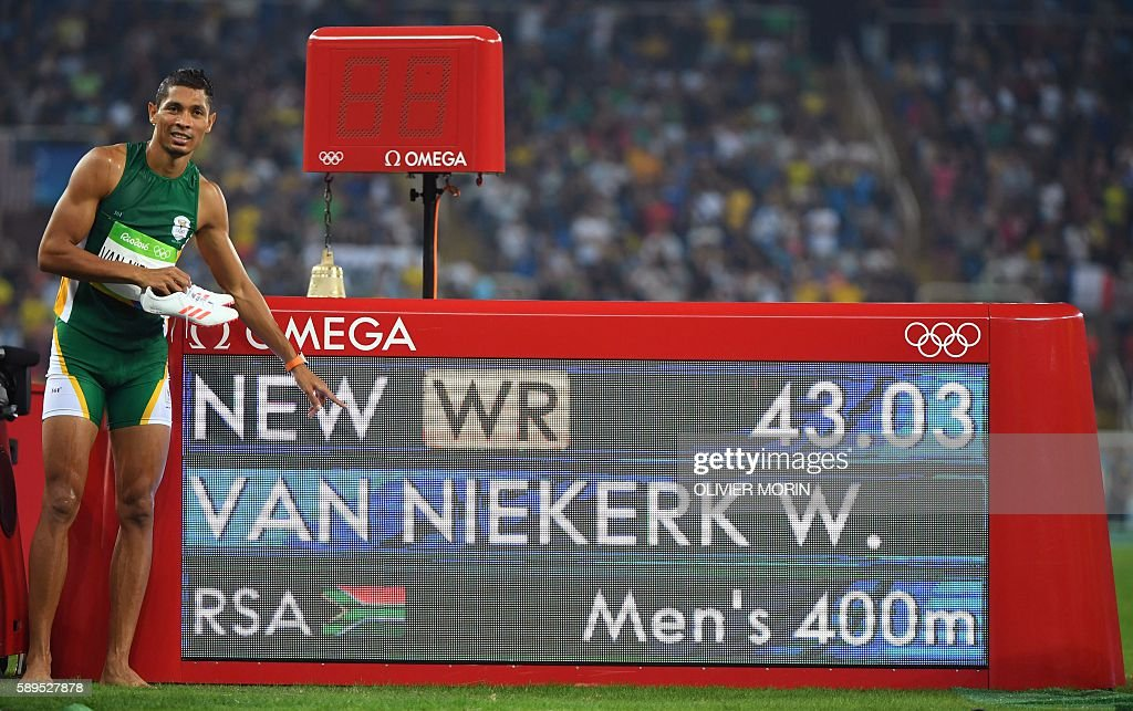 South Africa's Wayde van Niekerk poses by the results board after he broke the world record in the Men's 400m Final during the athletics event at the...