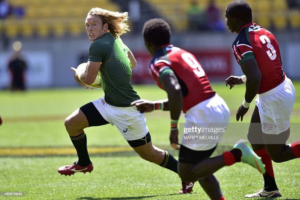 South Africa's Werner Kok is chased by Papua New Guinea's Henry Liliket and Dondon Kais during their Cup quarter final game on day two of the IRB...