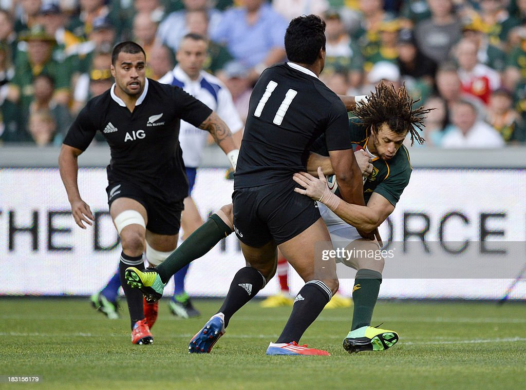 South Africa's Zane Kirchner (R) is tackled by New Zealand's Julian Savea (c) during the 2013 Rugby union test match South Africa vs New Zealand on October 5, 2013 at the Ellis Park Stadium in Johannesburg. AFP PHOTO / STRINGER