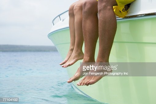 South American couple dangling feet off of boat : Stock Photo