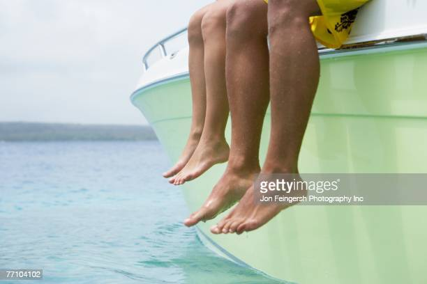 South American couple dangling feet off of boat