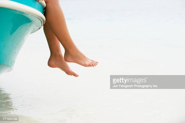 South American woman dangling feet off of boat