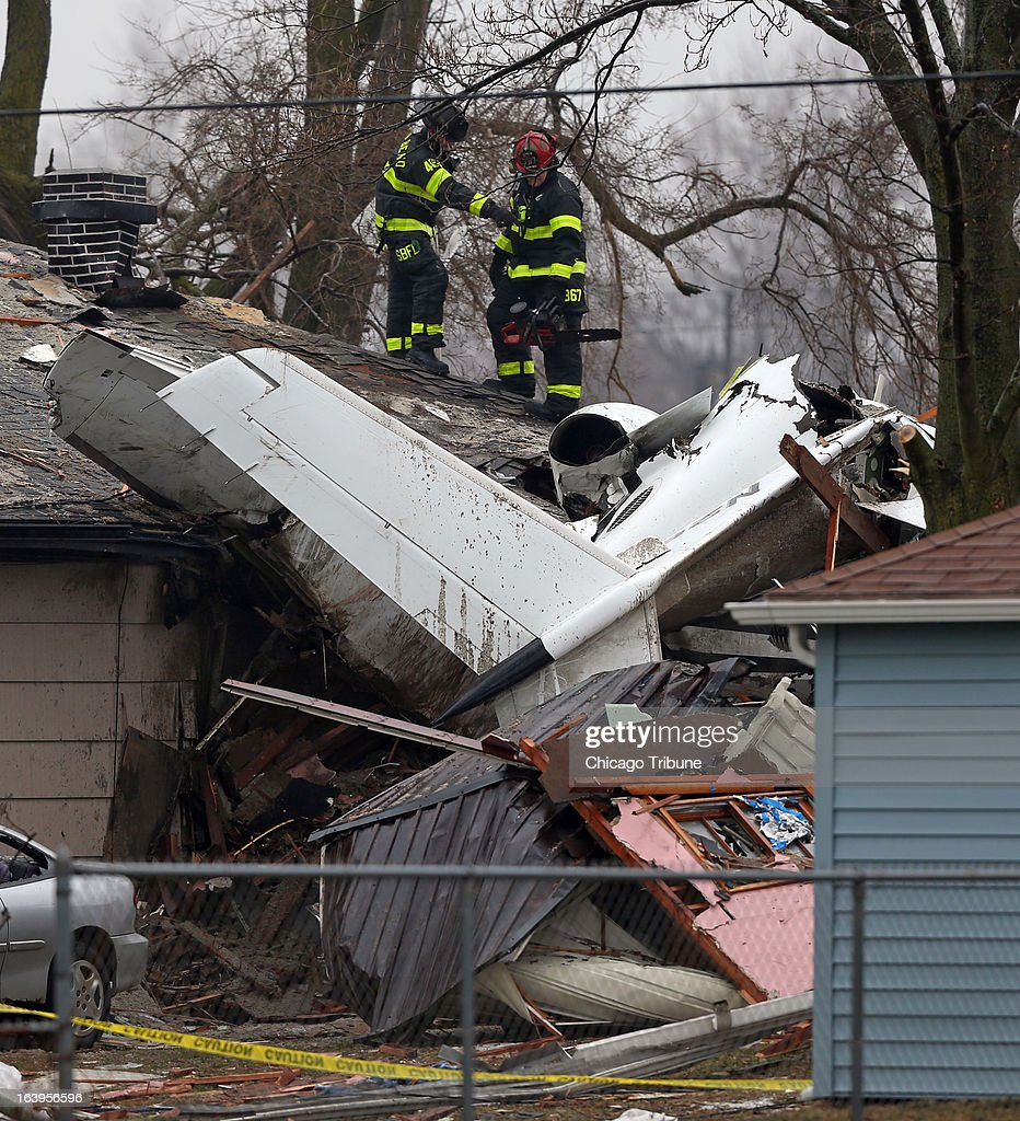 South Bend firefighters look over the wreckage of a small jet on Monday, March 18, 2013, that crashed Sunday near the South Bend Airport in South Bend, Indiana.