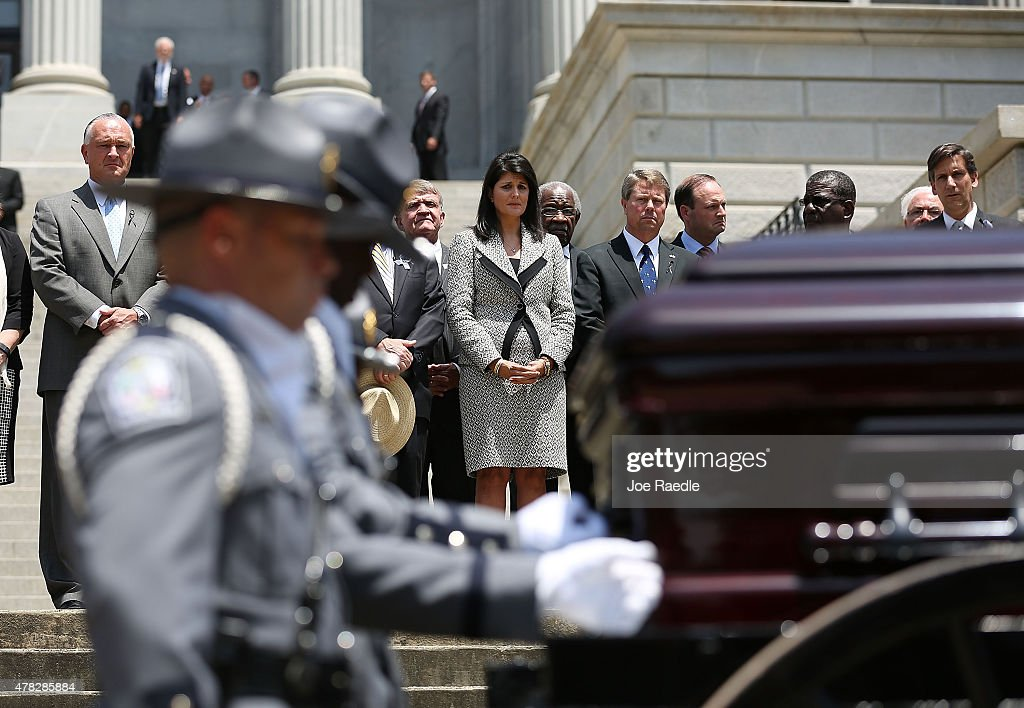 South Carolina Governor <a gi-track='captionPersonalityLinkClicked' href=/galleries/search?phrase=Nikki+Haley+-+Governor&family=editorial&specificpeople=6974701 ng-click='$event.stopPropagation()'>Nikki Haley</a> looks on as she stands with other lawmakers as South Carolina Highway Patrol Honor Guard prepare to carry the coffin of church pastor and South Carolina State Sen. Clementa Pinckney to lie in repose at the Statehouse Rotunda on June 24, 2015 in Columbia, South Carolina. Pinckney was one of nine people killed during a Bible study inside Emanuel AME church in Charleston. U.S. President Barack Obama and Vice President Joe Biden are expected to attend the funeral which is set for Friday June 26 at the TD Arena.