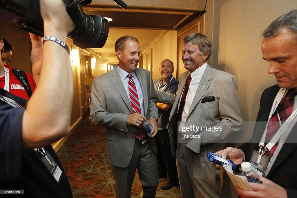South Carolina head coach Steve Spurrier talks with Ole Miss head coach Hugh Freeze during SEC football media days in Hoover, Alabama, Tuesday, July 16, 2013.