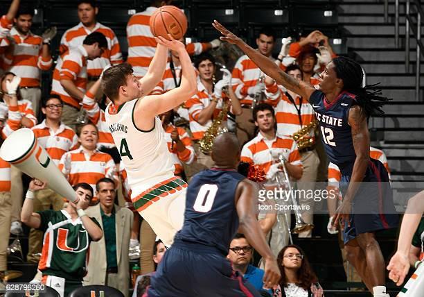 South Carolina State guard Tarik Clement defends the shot of Miami guard Dejan Vasiljevic during an NCAA basketball game between the South Carolina...