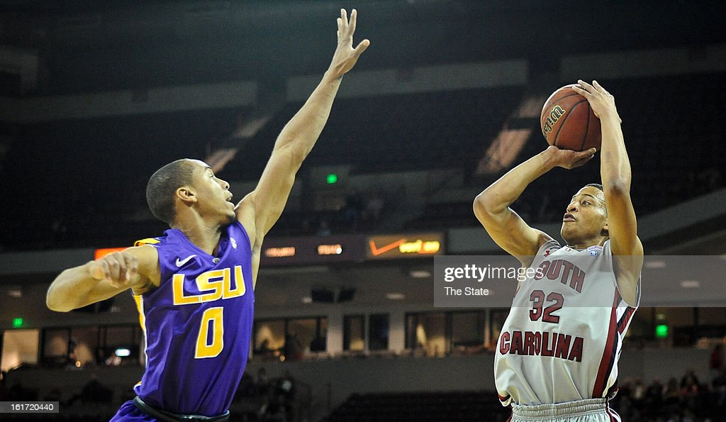 South Carolina's Damien Leonard hits a 3-pointer in the first half under pressure from Louisiana State's Charles Carmouche (0) at Colonial Life Arena in Columbia, South Carolina, on Thursday, February 14, 2013. LSU pulled away for a 64-46 win.
