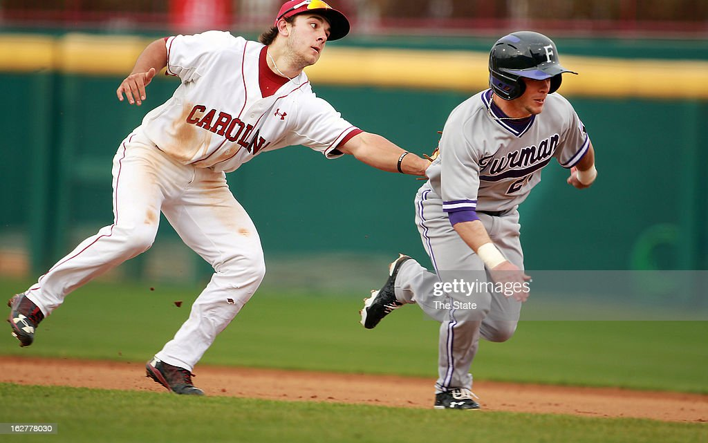 South Carolina's Max Schrock tags Furman's Heath Burton as he tries to make it back to first base in the third inning at Carolina Stadium in Columbia, South Carolina, Tuesday, Feburary 26, 2013.