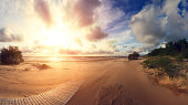 Sunset at south beach. South coast at the sunset. Bright evening sun shines at golden sand. Wooden path on beach. Beautiful resort background.