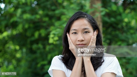 South East Asian girl looking at camera green background : Stock Photo