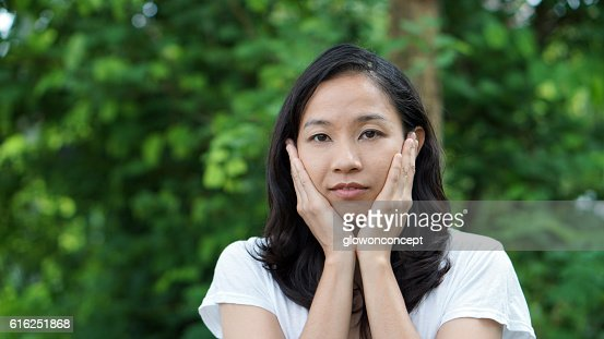 South East Asian girl looking at camera green background : Foto de stock