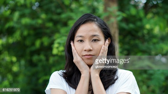 South East Asian girl looking away green background : Foto de stock