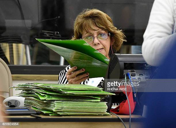A South Florida polling center worker stacks ballot sleeves as people wait to receive their ballots at an early voting centre in Miami Florida on...