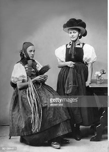 on the right a woman from the Gutach Valley in traditional Sunday costume and 'Bollenhut' hat on the left a countrywoman from St Georgen around 1910