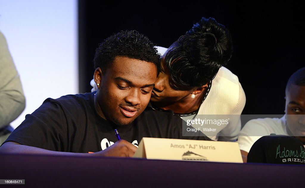 South High School football player Amos 'AJ' Harris gets a kiss from his mother, Tina, during a signing day ceremony in Denver, CO February 06, 2013. Harris signed with Adams State University.
